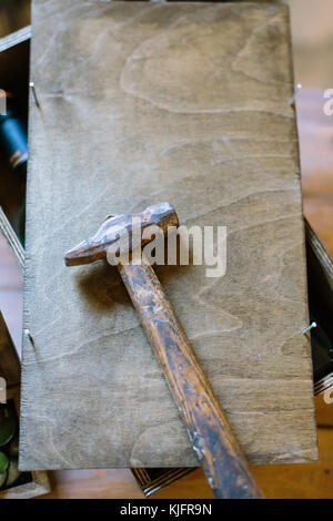 crafting, creativity, handmading concept. there is wooden box with small unclogged nails and big hammer for repairing - Stock Photo