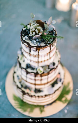 confectionary, cooking, handmade concept. close up of treat for wedding, richly decorated cake with dark frosting, - Stock Photo