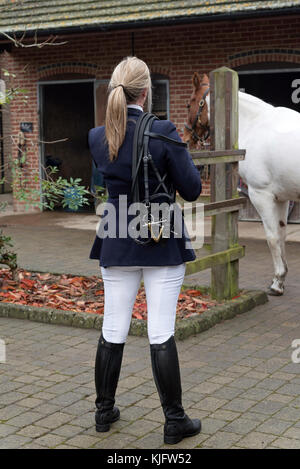 Blond woman horse rider standing in stable yard with a bridle over her shoulder. November 2017 - Stock Photo