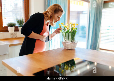 Pregnant woman taking care of flowers - Stock Photo