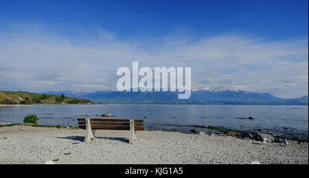 Lake scenery with a bench at summer day in New Zealand. - Stock Photo