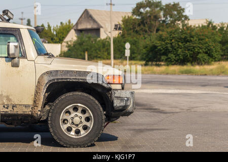 Side view of offroad car's wheel soiled in mud and dirt after trophy all-terrain competition in rural area . - Stock Photo
