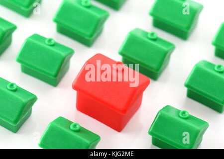 Large red house standing out from small green houses - Stock Photo