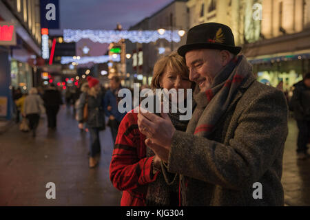 Mature couple are in the city centre on an evening at Christmas time. They are using a smart phone to take a selfie - Stock Photo