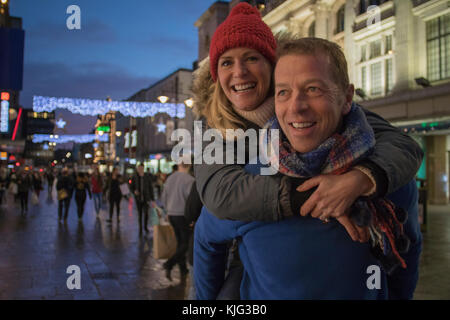 Mature man is giving his wife a piggy back through the city centre at Christmas time.