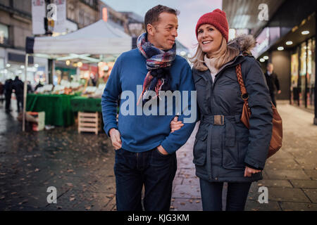 Mature coup;le are enjoying an evening stroll through the city christmas market. - Stock Photo