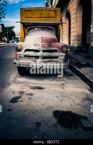 dirty red and yellow painted vintage Cuban truck parked in downtown Havana, Cuba - Stock Photo