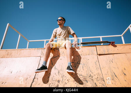 Young man with earbuds and longboard sitting on top of halfpipe in skatepark - Stock Photo
