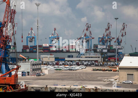 The Port of Ashdod in Israel with several large container handling cranes, vehicles on the dockside and shipping - Stock Photo