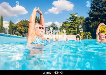 Group of seniors doing water gymnastics in pool - Stock Photo
