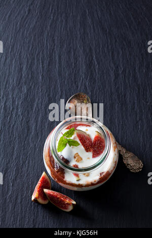 Glass of Mascarpone cream with fig compote and walnuts on slate - Stock Photo