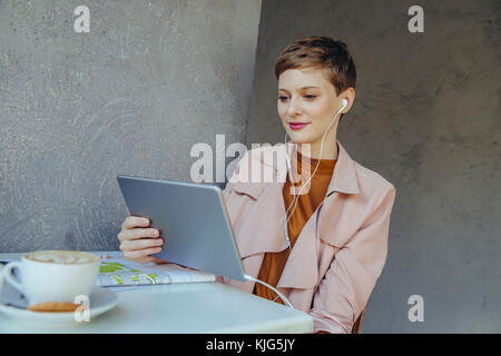 Woman with tablet and earbuds in a cafe - Stock Photo