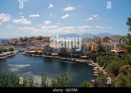 View of colorful houses in Agios Nikolaos, Crete, Greece, and mountain range - Stock Photo