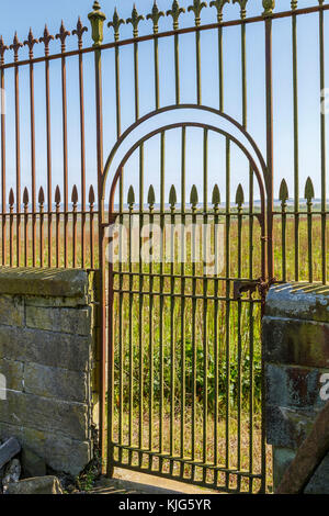 Iron gateway within the framework of a wrought iron fence and traditional stone wall, Wigtown, Scotland, UK. - Stock Photo