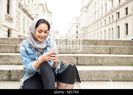 London, UK, England, Pretty muslim girl chatting over the phone wearing hijab in the street, muslim university student - Stock Photo