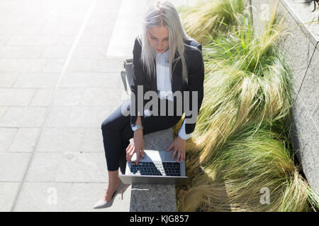 Young businesswoman sitting on a wall in the city using laptop - Stock Photo