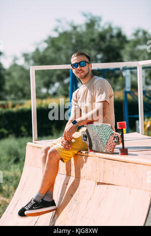 Smiling young man with earbuds and longboard sitting on top of halfpipe in skatepark - Stock Photo