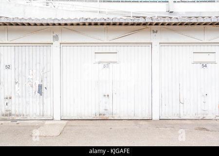 Row of three white garage doors - Stock Photo