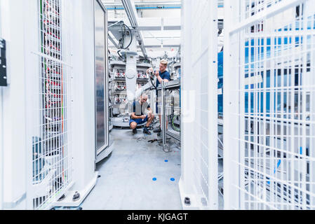 Two colleagues working at industrial robot in modern factory - Stock Photo