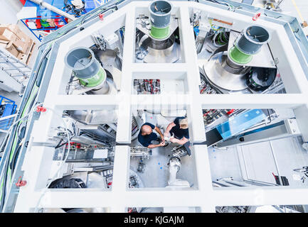 Top view of two colleagues working at industrial robot in modern factory - Stock Photo