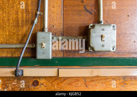 Two vintage light switches on a wooden wall - Stock Photo