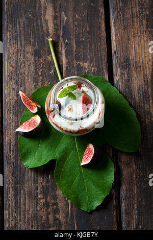 Glass of Mascarpone cream with fig compote and walnuts on fig leaf and dark wood - Stock Photo