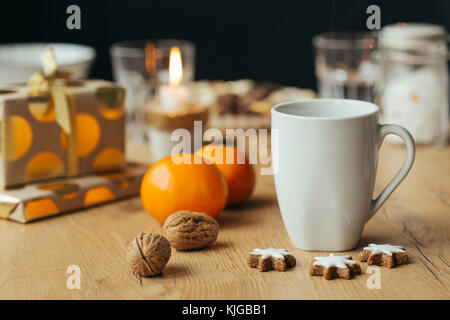 Cup of tea, tangerines, walnuts,  cinnamon stars and Christmas presents in the background - Stock Photo