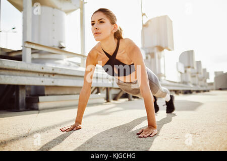Young woman doing pushups in the city - Stock Photo