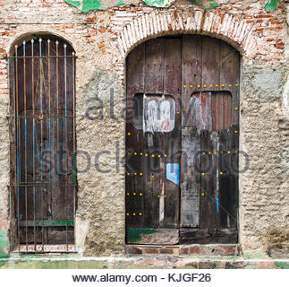 Dilapidated building with two arched wooden doors and bricks showing up from under the broken plaster. Old vintage - Stock Photo