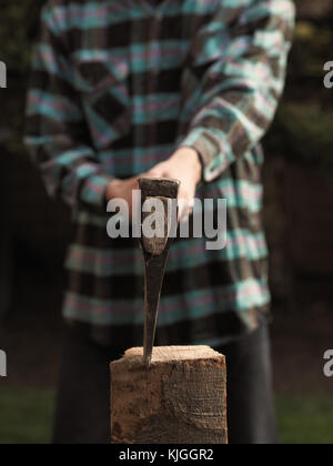 Close up shot of a man cutting fire wood, selective focus on the axe - Stock Photo
