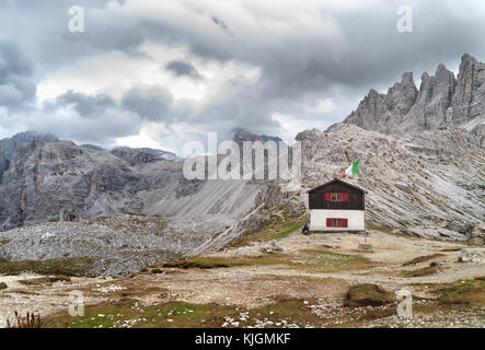 Small old hut on the edge of Mount Paterno next to Dreizinnen hut with Italian flag in front, Dolomites, Italy - Stock Photo