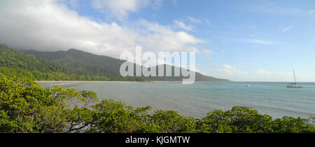 View of rainforest under dark clouds and a sailing ship from Cape Tribulation lookout, Australia - Stock Photo