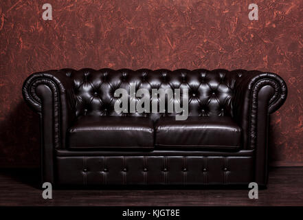 Vintage old dark brown leather sofa with grunge brown wall in the living room - Stock Photo