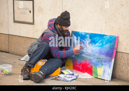 Manchester, UK. 24th Nov, 2017. Homeless man, a street artist in the city centre on Black Friday which has become - Stock Photo