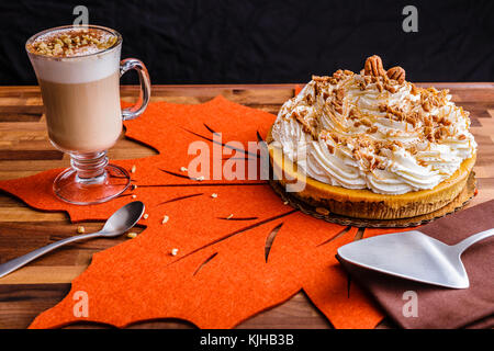 Enjoy Thanksgiving with a pumpkin pie cheesecake and a cup of latte coffee.  Setting on an orange leaf placemate - Stock Photo
