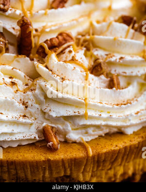 Enjoy Thanksgiving with a pumpkin pie cheesecake.   Cheesecake is covered with whipped cream and pecans, then drizzled - Stock Photo