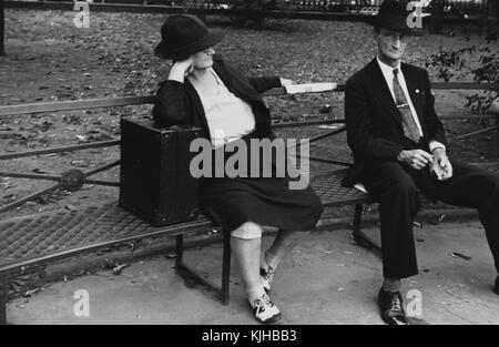 A photograph of a man and woman sitting on a metal park bench, the woman wears a jacket, skirt, and hat, she is - Stock Photo