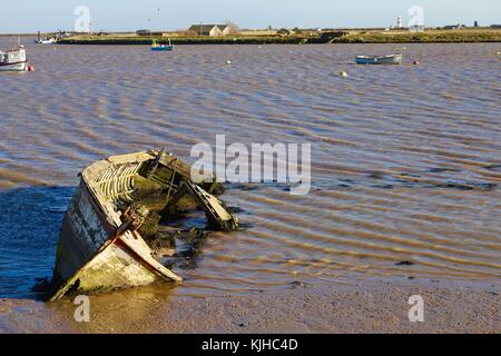 A derelict abandoned wooden boat on its side in the muddy River Alde at Orford Quay. Suffolk, UK. - Stock Photo