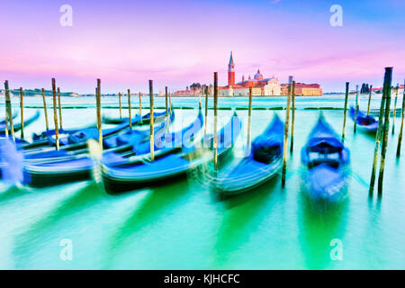 Gondolas moving along the wave on the Grand Canal in Venice at dusk. - Stock Photo