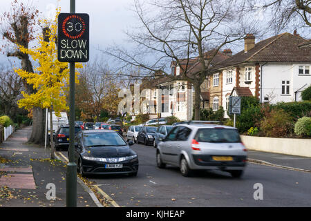 A car (motion blurred) speeds past an illuminated vehicle activated speed sign on a suburban residential road - Stock Photo