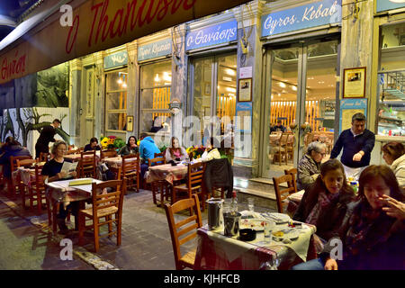 Evening sitting outside at Greek restaurant in popular picturesque Plaka district of central Athens near Monastiraki - Stock Photo
