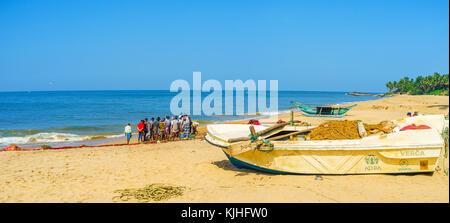 BENTOTA, SRI LANKA - DECEMBER 6, 2016: Panorama of the scenic sand beach with a group of fishermen, standing around - Stock Photo