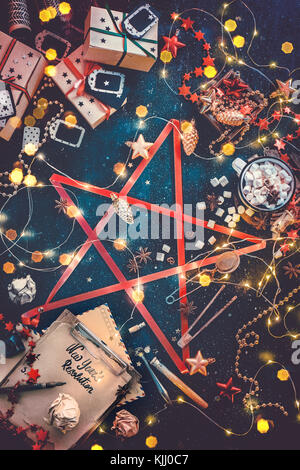 Star of Christmas essentials. Decorations, gift boxes, fairy lights, new year resolution notebook and hot chocolate - Stock Photo