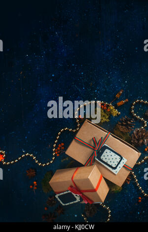 Christmas gift boxes. Decorations and wrapped presents concept. Christmas celebration dark flat lay with craft paper - Stock Photo