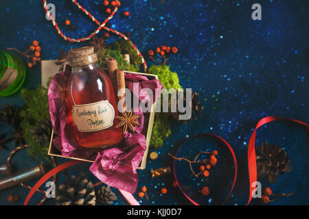 Present box with a bottle of Luck Potion. Magical still life with potion bottles, ingredients and steam. Best wishes - Stock Photo