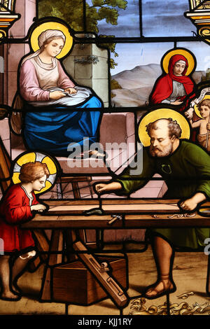 Saint Martin church.  Stained glass window.  the Holy Family in Saint Joseph's carpentry workshop. Avallon. France. - Stock Photo
