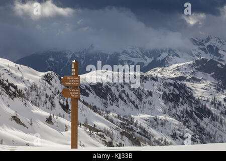 Footpath sign on the Col de la Lombarde or Colle della Lombarda, on the French-Italian border in spring; looking - Stock Photo