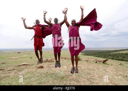 Masai warriors doing the traditional jump dance.  Masai Mara game reserve. Kenya. - Stock Photo