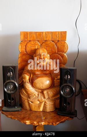 Laughing Buddha statue and speakers. Battambang.  Cambodia.