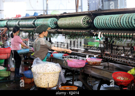 Traditional silk factory.  Woman working on silk spinning machine.  Dalat. Vietnam. - Stock Photo